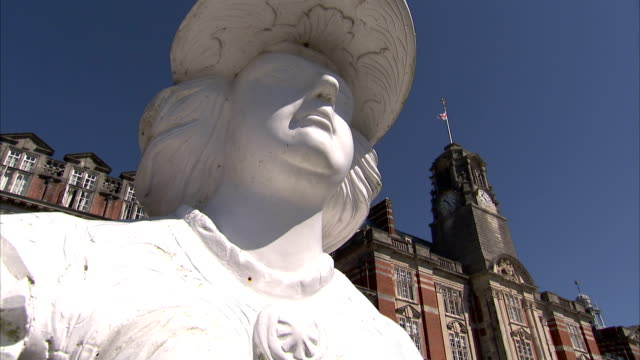 A bright white statue stands in front of a building on the campus of Britannia Royal Naval College. Available in HD.