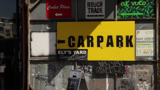 A bright yellow sign reading 'CAR PARK' hangs amid signs advertising local businesses on Brick Lane, Tower Hamlets, East London.
