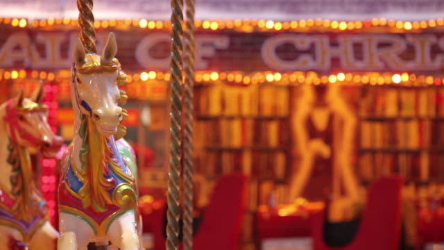 a brightly coloured carousel starts to turn at a funfair. - 回転遊具点の映像素材/bロール