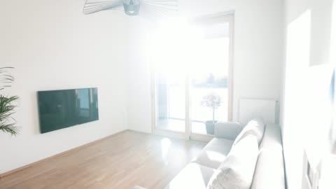 ljusa vardagsrum i en öppen planlösning lägenhet med minimalistisk inredning - boningsrum bildbanksvideor och videomaterial från bakom kulisserna