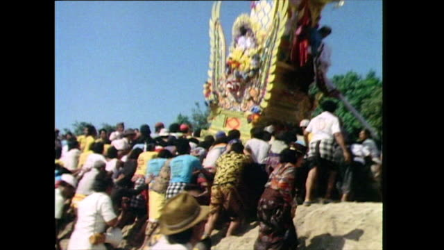 a brightlycoloured waddhu tower is followed by hundreds of people and carried over the beach during a traditional balinese funeral procession in bali... - pacific islander stock videos & royalty-free footage