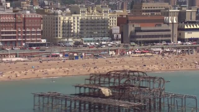 east sussex brighton brighton pier / busy brighton beach on a hot and sunny day / people sunbathing relaxing in groups and swimming in the sea - east sussex stock videos & royalty-free footage