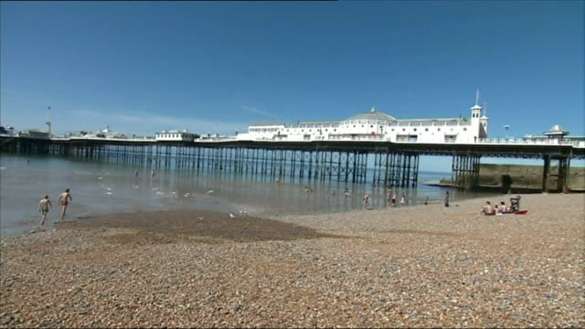brighton beach general views; england: sussex: brighton: ext brighton beach with brighton pier / big wheel with beach in foreground - ブライトン パレスピア点の映像素材/bロール