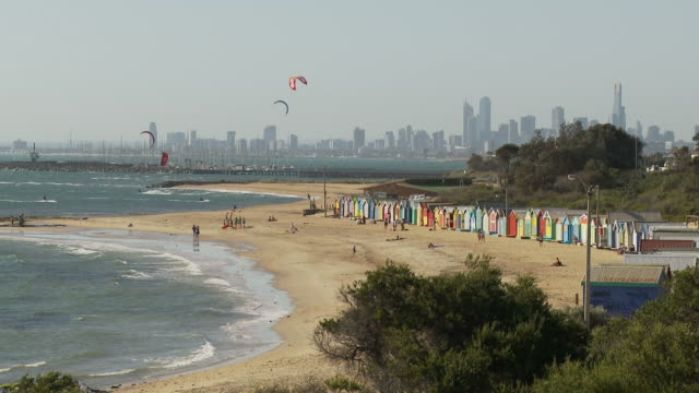 ws brighton beach with beach huts and kite surfers, downtown skyline in background / melbourne, australia - bay of water stock videos & royalty-free footage