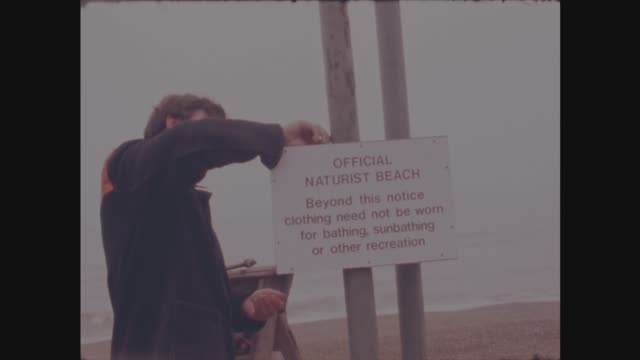 Brighton EXT Man puts up notice 'Official Naturist Beach' Workmen build a sign 'Public Notice clothes need not be worn'