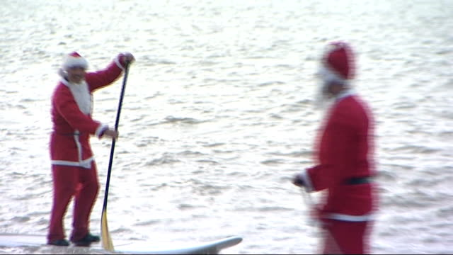 Brighton Swimming Club Christmas Day swim in English Channel ENGLAND East Sussex Brighton EXT Swimmers on beach wearing Santa hats / Various shots...