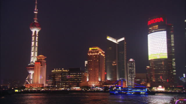 brilliant neon lights illuminate water front skyscrapers and ferry boats in shanghai. - 東方明珠塔点の映像素材/bロール