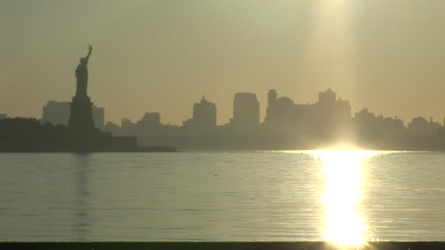 a brilliant sun casts golden light across the new york city skyline and the statue of liberty. - statue of liberty new york city video stock e b–roll