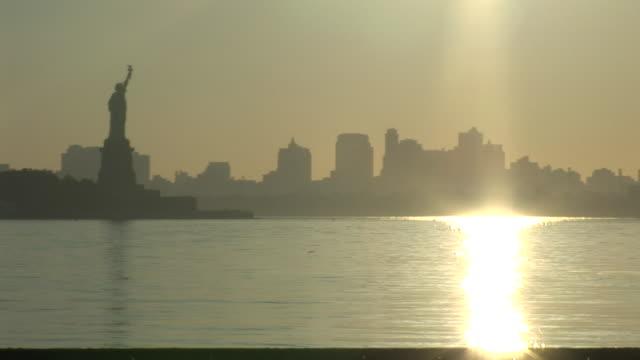 a brilliant sun casts golden light across the new york city skyline and the statue of liberty. - porto di new york video stock e b–roll
