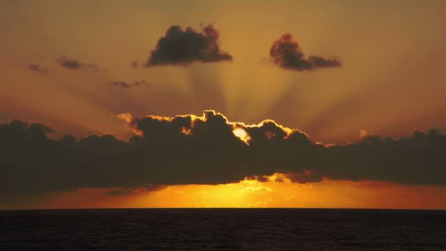 A brilliant sun glows behind thick clouds above an ocean horizon.