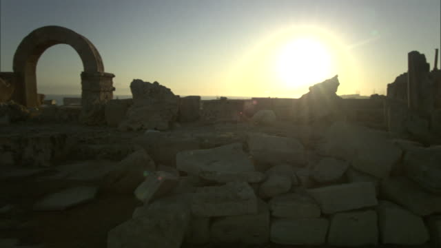 a brilliant sun rises above the roman ruins of leptis magna in libya. - ancient rome stock videos & royalty-free footage
