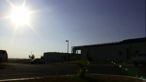 a brilliant sun shines above a building and parking lot in panama. - heat stock videos & royalty-free footage