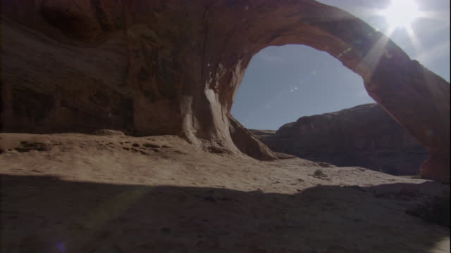 A brilliant sun shines above a limestone arch and desert in Utah. Available in HD.