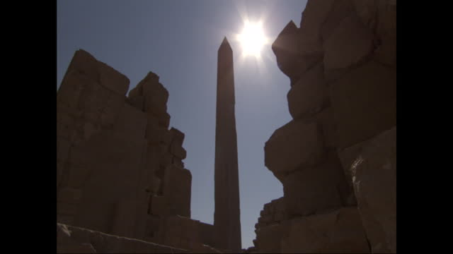 a brilliant sun shines above an obelisk and ruins in egypt. - obelisk stock-videos und b-roll-filmmaterial