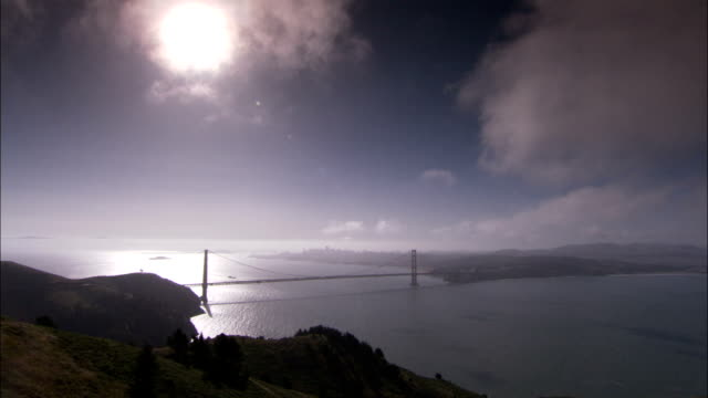 a brilliant sun shines above the golden gate bridge and san francisco bay. available in hd. - golden gate bridge stock-videos und b-roll-filmmaterial
