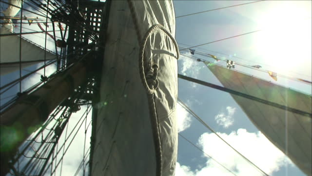 a brilliant sun shines above the shrouds and sails of a tall ship. - schiffsmast stock-videos und b-roll-filmmaterial