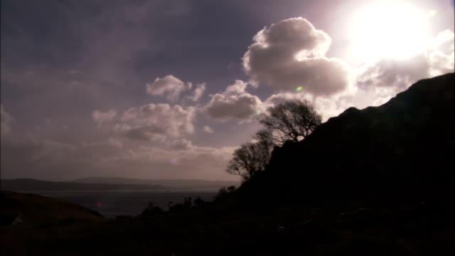 vídeos de stock, filmes e b-roll de a brilliant sun shines in a cloudy sky. - espaço e astronomia