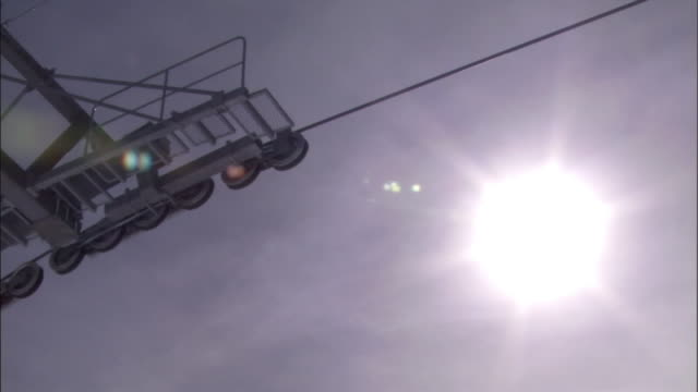 a brilliant sun shines over a ski lift. - ski lift stock videos & royalty-free footage