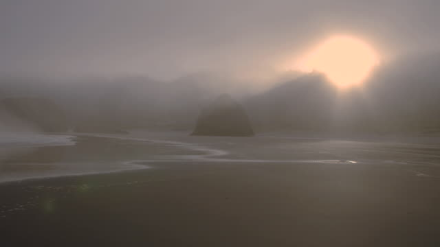 a brilliant sun shines though heavy fog on the oregon coast near the pistol river. - heceta head stock videos & royalty-free footage