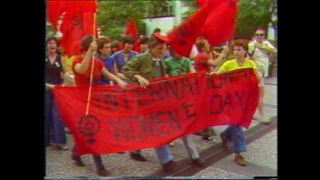 brisbane international womens day march women chanting and marching behind red banner and with red flags / police and policewomen stand by /... - internationaler frauentag stock-videos und b-roll-filmmaterial