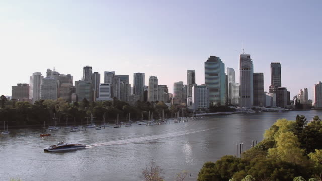 Brisbane skyline at sunset with a boat in the river