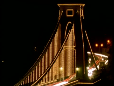 t/l bristol clifton suspension bridge at night - ms lit supporting pillar of bridge, streaky traffic crossing brightly lit bridge - clifton suspension bridge stock videos and b-roll footage