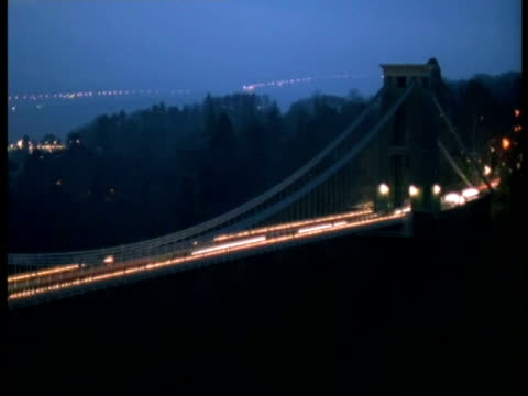 t/l bristol clifton suspension bridge at night - pan left across bridge, streaky traffic, city lights in background, bridge lights come on - clifton suspension bridge stock videos and b-roll footage