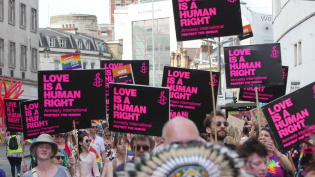 parade marching through city centre with love is a human right signs - uguaglianza video stock e b–roll