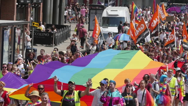 parade marching with lgbt rainbow flag through city centre - pride stock videos & royalty-free footage