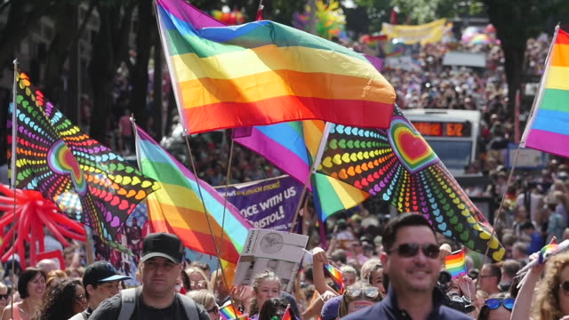 vidéos et rushes de parade marching with lgbt rainbow flags through city centre - fierté