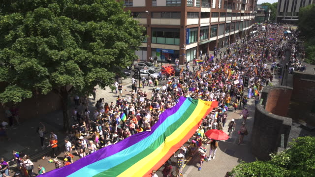 parade marching with lgbtq rainbow flag through city centre - pride stock videos & royalty-free footage