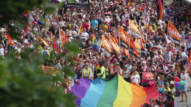 vidéos et rushes de parade marching with lgbtq rainbow flag through city centre - trans