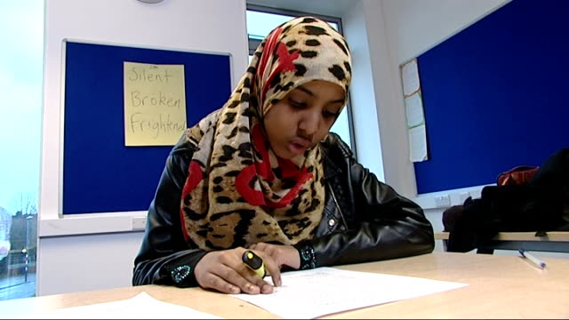 Bristol schoolgirl brings FGM campaign to Education Secretary Mohamed sitting at desk reading Various of Mohamed using yellow highlighter pen to mark...