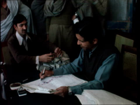 britain doubles aid to pakistan / afghan refugees; d: pakistan: north / west frontier: peshawar: ext gv form afghan mountains to camp tents people in... - 掘る点の映像素材/bロール