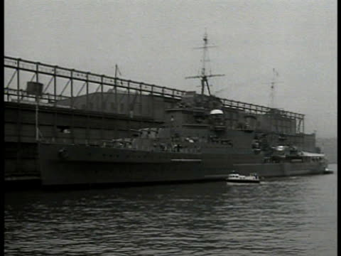britain navy battleship docked at pier. english sailors pulling rope on deck docking ship. sailors disembarking launch boat. world war ii war effort... - world war ii stock-videos und b-roll-filmmaterial