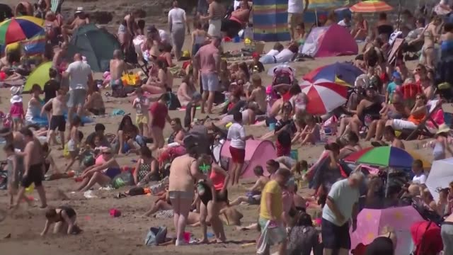 britain projected to break temperature records in heatwave; wales: glamorgan: barry: barry island: ext people on beach people paddling in sea crowds... - wales stock videos & royalty-free footage