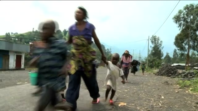 britain stops aid donation over support for drc rebels / t26111231 various of civilians along road carrying belongings as fleeing goma - rebellion stock-videos und b-roll-filmmaterial