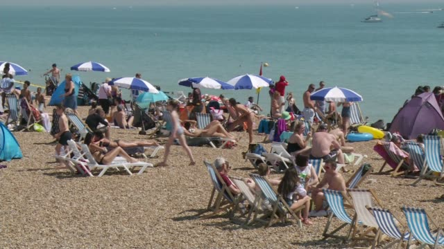 britain to see hottest june day since 1976 england ext various shots people on beach in heatwave - 1976 stock-videos und b-roll-filmmaterial
