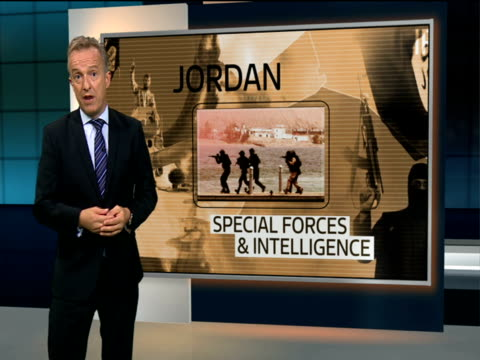 Britain to send weapons to be used against Islamic State in Iraq ENGLAND London GIR Reporter to camera with Videowall showing various footage behind