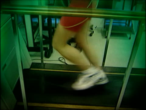 stockvideo's en b-roll-footage met britain told to get fit; itn england: london: int slow motion legs of person running on treadmill in gym - vrijetijdsfaciliteiten