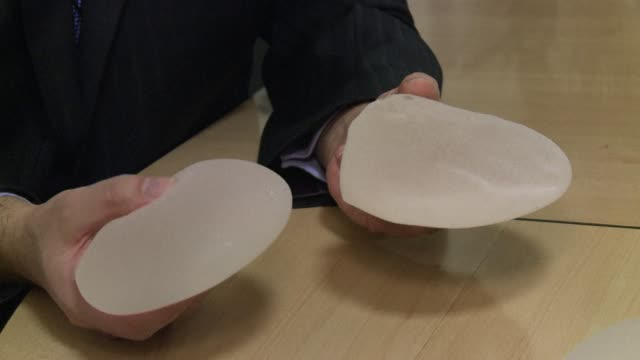 britain's chief medical officer said on friday the government was not advising some 42000 women with breast implants made by french firm pip to have... - breast augmentation stock videos and b-roll footage