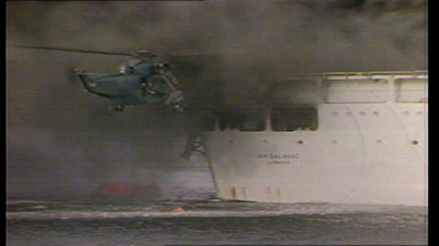 vídeos de stock e filmes b-roll de britain's search and rescue service sold off to us firm lib / tx bluff cove various shots of sea king helicopter alongside burning ship sir galahad... - ilhas malvinas