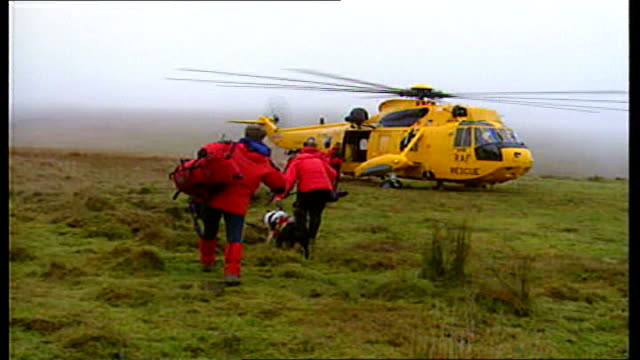 Britain's search and rescue service sold off to US firm LIB / TX Rescue workers with rescue dogs and rescued girls along towards helicopter...