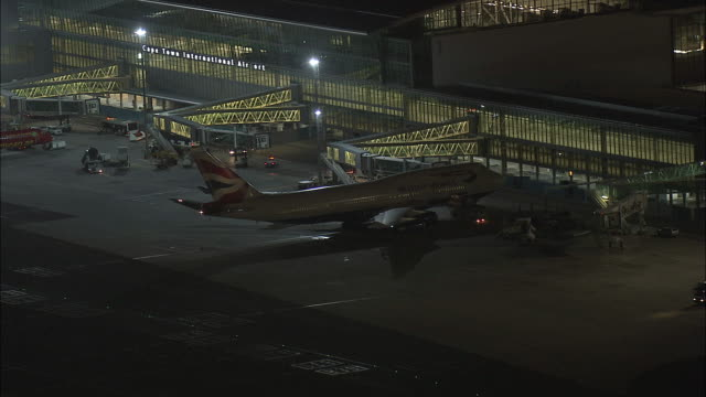 stockvideo's en b-roll-footage met aerial british airways 747 jet at departure gate of international airport, night, cape town, western cape, south africa - blijf staan