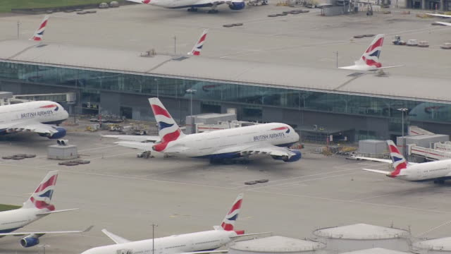 british airways aeroplanes grounded and parked up at airport during coronavirus pandemic - stationary stock videos & royalty-free footage