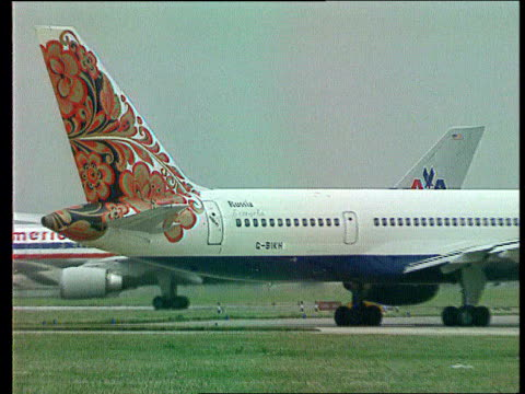 airways lib ext british airways aircraft with controversial tail fin design taxiing as others seen in b/g flower pattern on tailfin of aircraft zoom... - tail fin stock videos & royalty-free footage