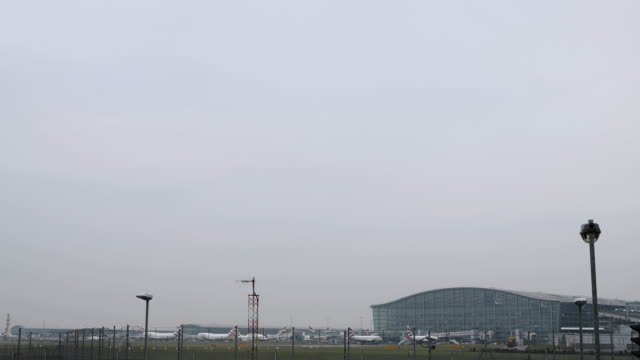 british airways airliner lands at heathrow airport with terminal 5 in the background on october 25, 2016 in london, england. - air vehicle stock videos & royalty-free footage