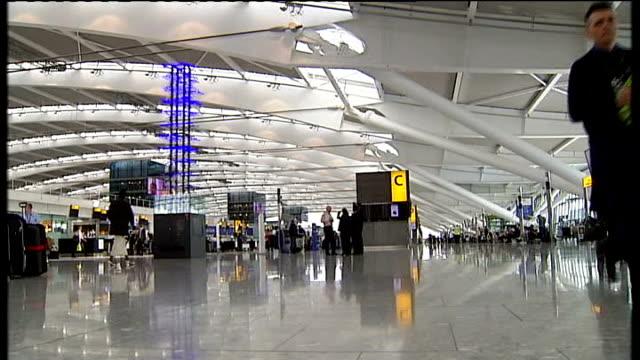 British Airways CEO refuses bonus **Willie Walsh interview overlaid** Passengers in Heathrow Terminal 5 checkin area