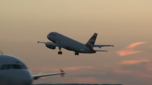 vídeos de stock e filmes b-roll de a british airways jet takesoff into a reddening dusk skyline after its departure as last flight out of heathrow's terminal one unidentifable as it... - lugar genérico