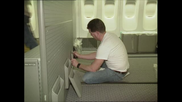 stockvideo's en b-roll-footage met boeing 777 usa seattle int engineer works on new boeing 777 plane gvs plane in hangar carpet laid on floor of plane woman laying carpet man painting... - new not politics